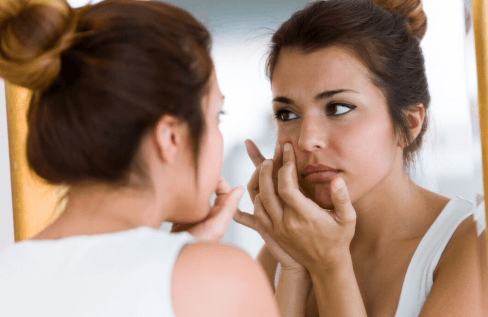 woman-looking-at-skin-in-mirror