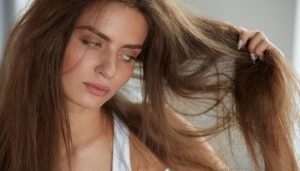 woman-holding-her-messy-brown-hair