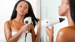 woman-drying-hair-in-mirror