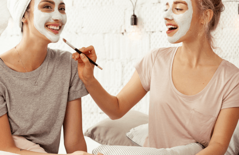 two-women-putting-on-face-masks-sitting-on-a-bed