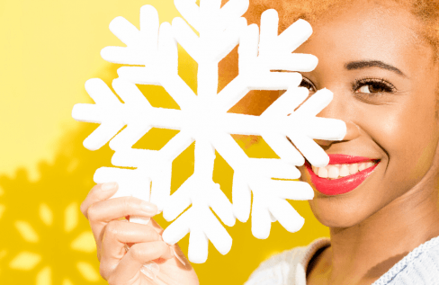 woman-holing-paper-snowflake-over-face-with-yellow-hair-on-yellow-background