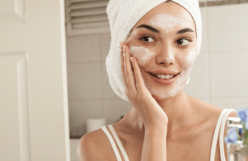 woman-applying-skincare-in-mirror